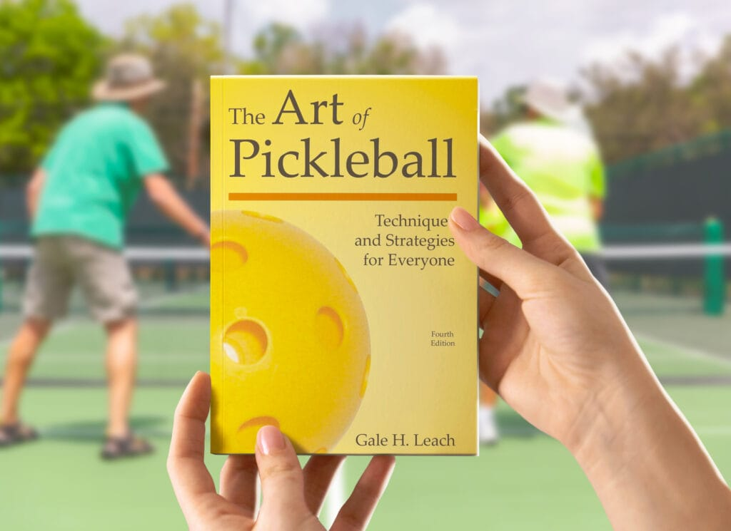 person holding a pickleball book in front of a pickleball court