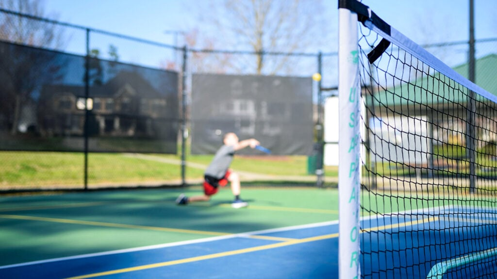 boy playing pickleball with a paddle, ball and net