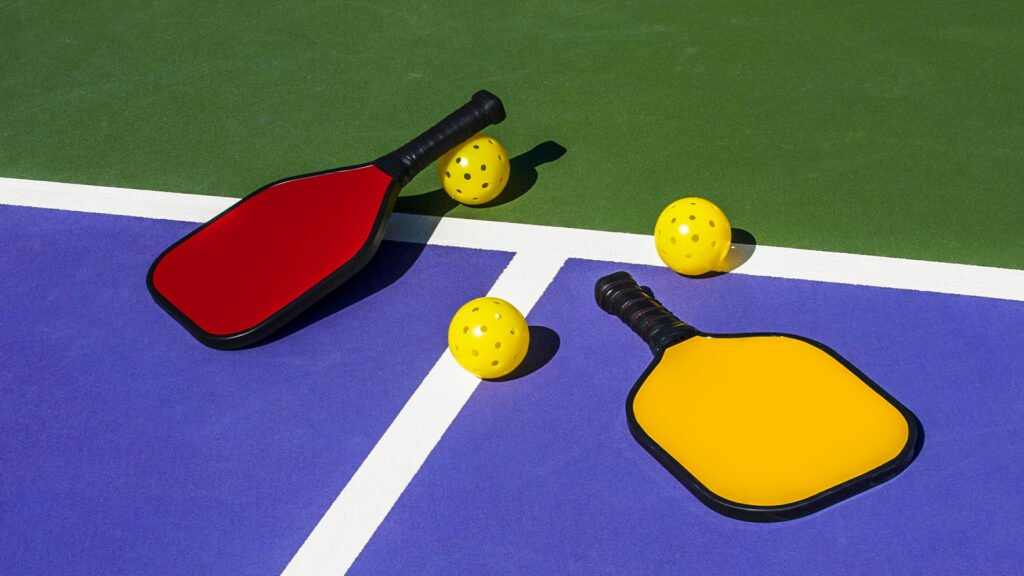 pickleball set of two paddles and two balls laid out on a pickleball court