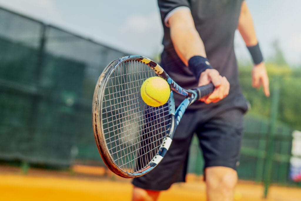 Close up of man playing tennis and beating the ball with a racket