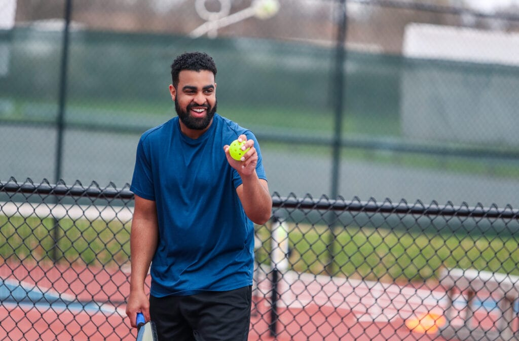 pickleball player smiling before serving