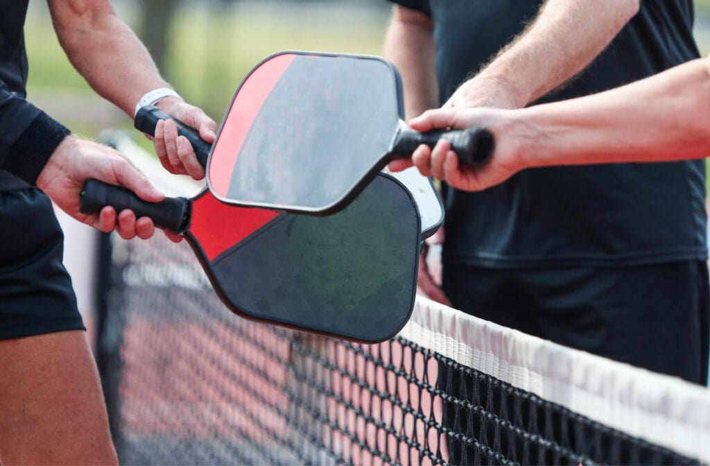 pickleball players touching paddles after a game