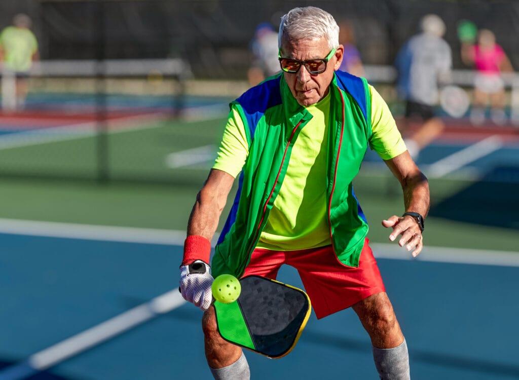 senior man playing pickleball